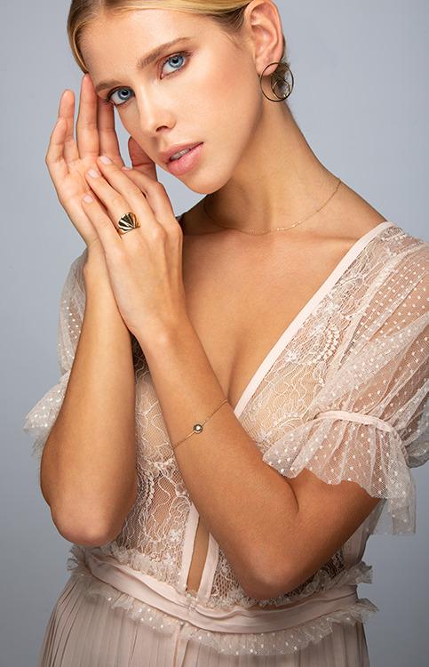 Femme blonde aux yeux bleus portant une robe dentelle blanche, des bijoux Laparitaine en or fin, bague Iris, bracelet Andréa nacre et boucles d'oreilles Neela