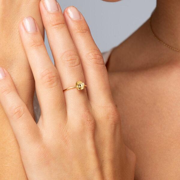 Main de femme portant une bague Hoani en or fin, ajustable, fleur