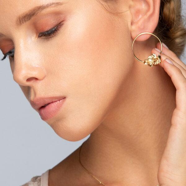 Femme blonde aux yeux bleus, avec boucles d'oreilles créoles Mélissa, fleurs