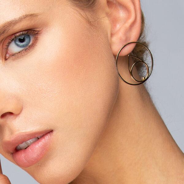 Laparitaine Femme blonde aux yeux bleus, avec boucles d'oreilles créoles Neela, forme géométrique, or fin, détails
