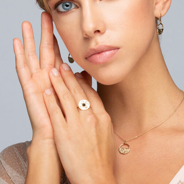 Femme blonde au yeux bleu sur fond gris portant une bague, collier, bracelet et boucles d'oreilles Laparitaine 2