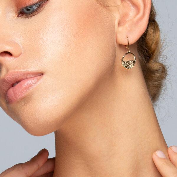 Femme blonde aux yeux bleus, portant une paire de boucles d'oreilles créoles Léna, dorée à l'or fin, feuille d'or
