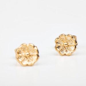 Gros plan sur une paire de boucle d'oreille puce Mya doré à l'or fin, fleur