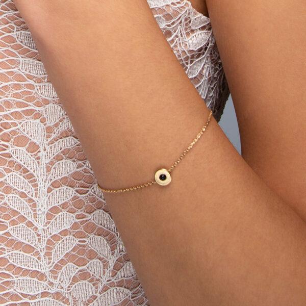 Femme portant une robe dentelle blanche et un bracelet Andréa en or fin, chaîne, cabochon pierre précieuse en quartz noir 2 Laparitaine